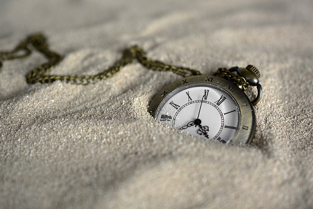 An image of a pocket watch laying in sand.